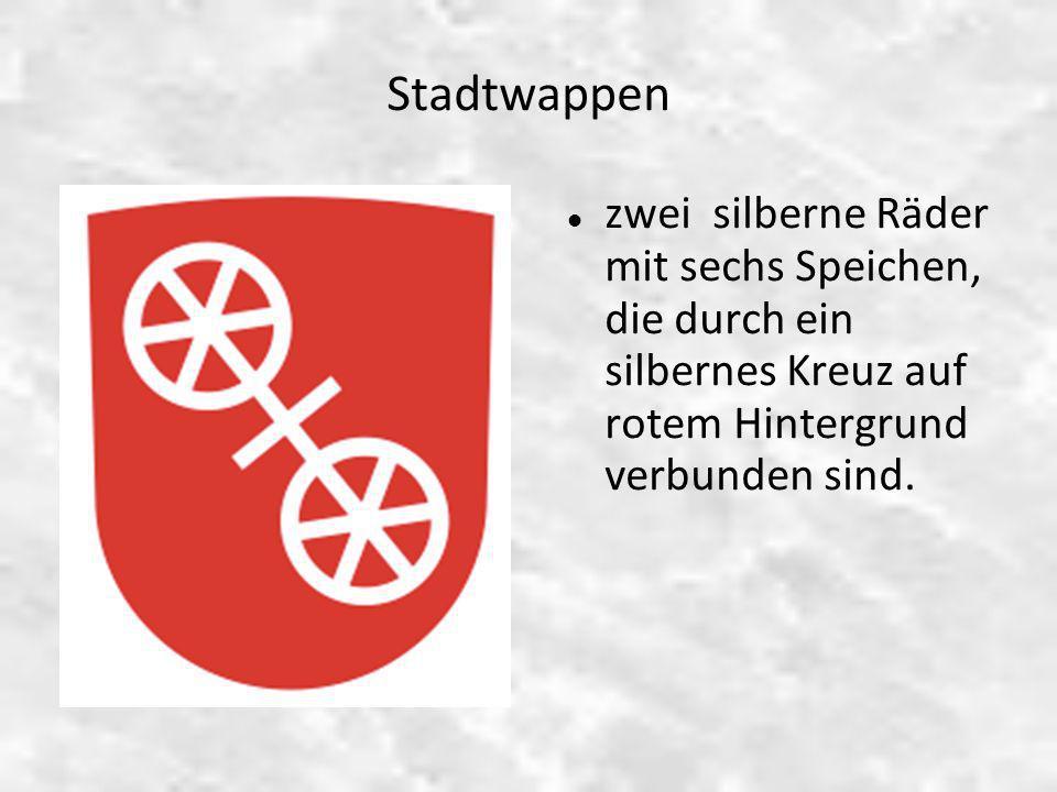 Stadtwappen zwei silberne Räder mit sechs Speichen, die durch ein silbernes Kreuz auf rotem Hintergrund verbunden sind.