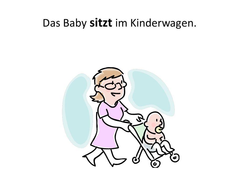 Das Baby sitzt im Kinderwagen.