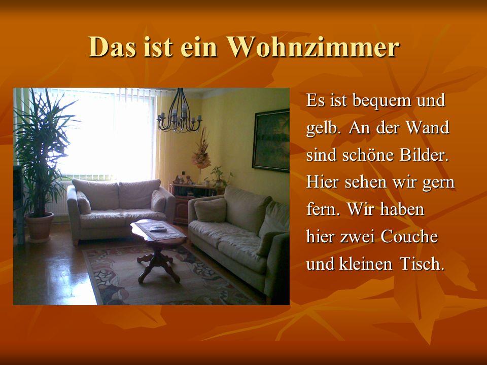 Das ist ein Wohnzimmer Es ist bequem und gelb. An der Wand