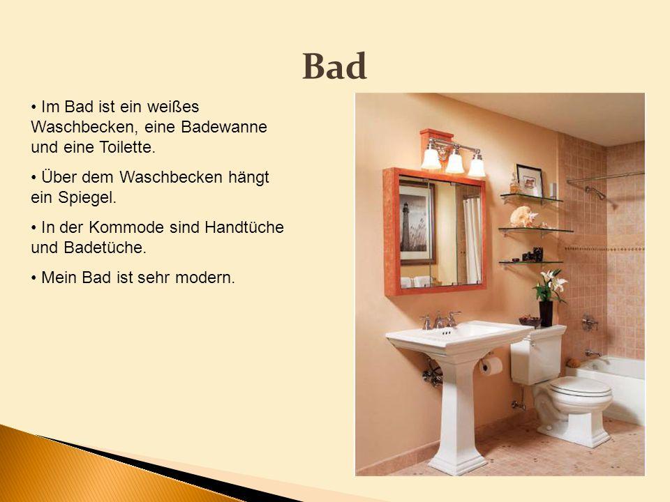 BadIm Bad ist ein weißes Waschbecken, eine Badewanne und eine Toilette. Über dem Waschbecken hängt ein Spiegel.