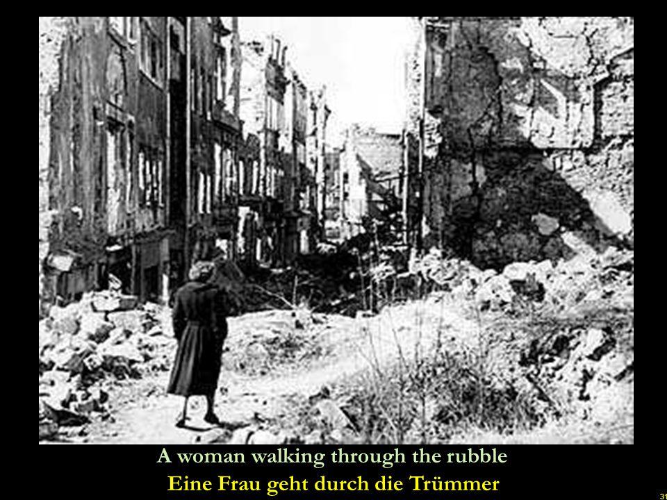 Eine Frau geht durch die Trümmer