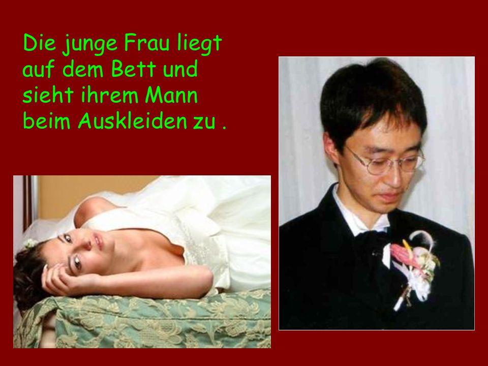 Die junge Frau liegt auf dem Bett und sieht ihrem Mann beim Auskleiden zu .