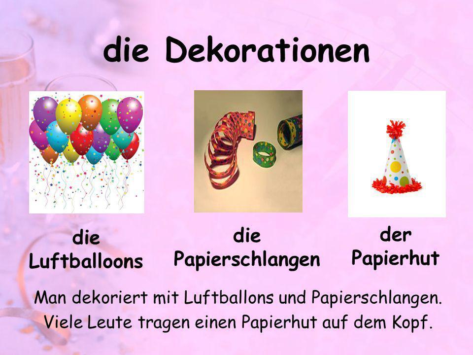 die Dekorationen die Papierschlangen der Papierhut die Luftballoons