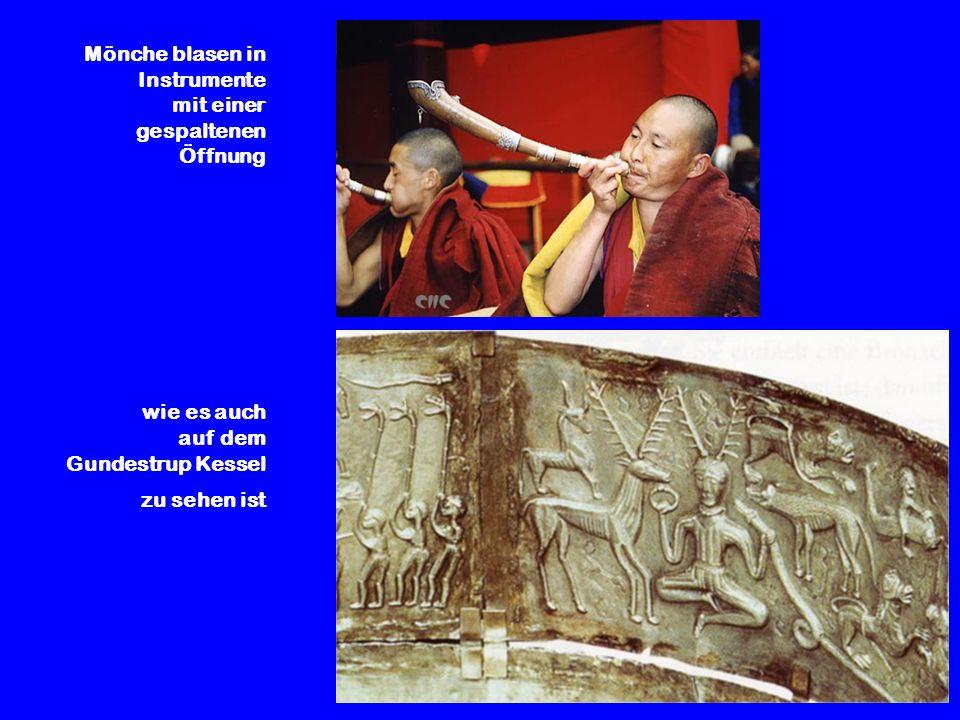 Mönche blasen in Instrumente mit einer gespaltenen Öffnung